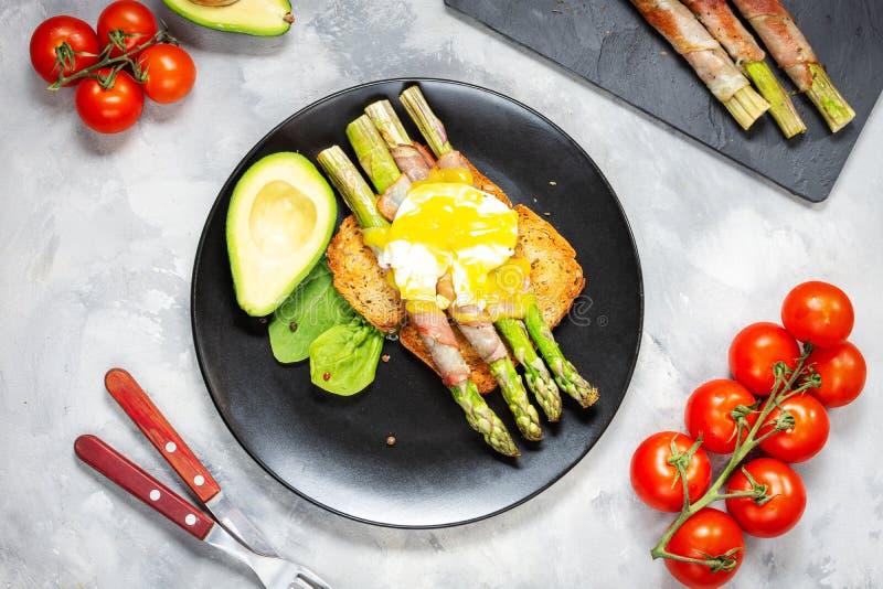 De geroosterde groene asperge die met bacon, Benedict wordt verpakt stroopte ei en avocado op toosts voor ontbijt royalty-vrije stock foto's