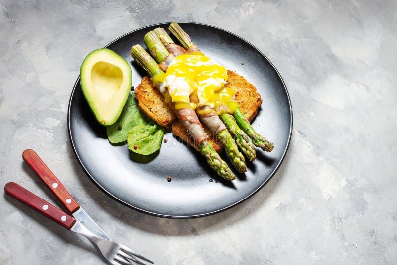 De geroosterde groene die asperge met bacon, Benedict wordt verpakt stroopte ei en avocado op toosts royalty-vrije stock foto's