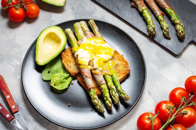 De geroosterde groene die asperge met bacon, Benedict wordt verpakt stroopte ei en avocado op toosts stock afbeeldingen