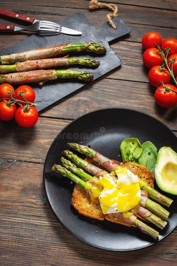 De geroosterde groene die asperge met bacon, Benedict wordt verpakt stroopte ei en avocado op toosts stock foto's