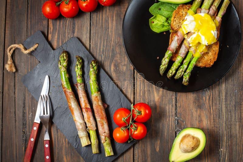 De geroosterde groene die asperge met bacon, Benedict wordt verpakt stroopte ei en avocado op toosts voor ontbijt royalty-vrije stock fotografie