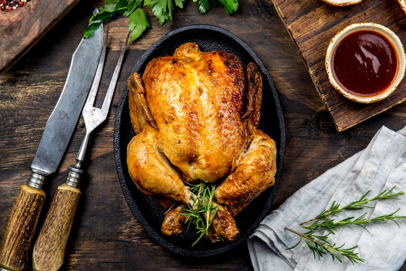 De geroosterde kip met rozemarijn diende op zwarte plaat met sausen op houten lijst, hoogste mening stock afbeeldingen