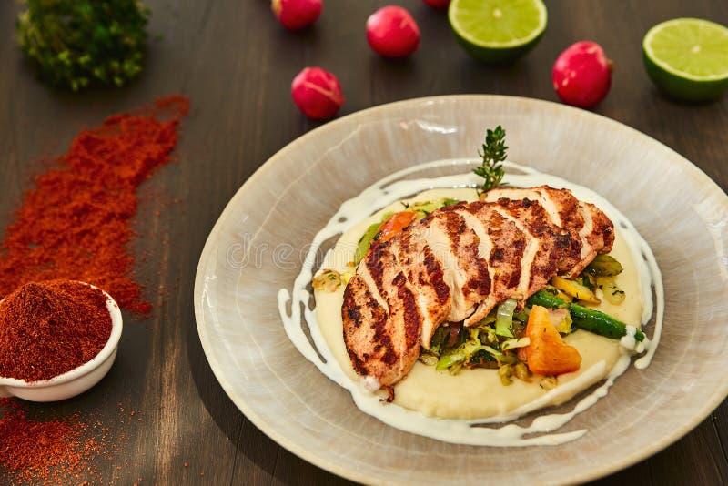 De geroosterde kippenfilet wordt gesneden in plakken op een kussen van fijngestampte aardappels met groenten - ui, knoflook, pepe royalty-vrije stock fotografie