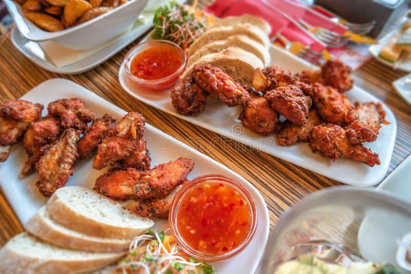 De geroosterde kippenvleugels, gebakken westelijke aardappels, zoete Chinees pekelen en verse salade in openluchtrestaurant royalty-vrije stock fotografie