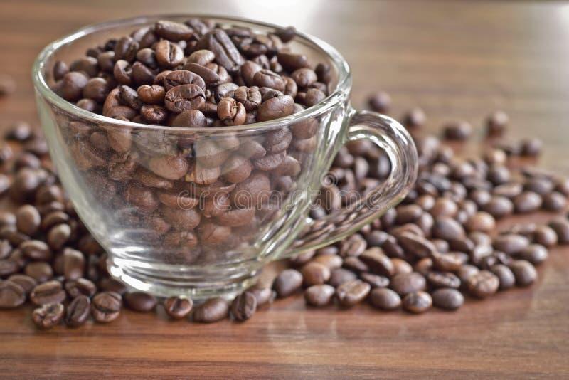 De geroosterde koffiebonen in een kop en een hoop van koffie zetten op houten t royalty-vrije stock afbeeldingen