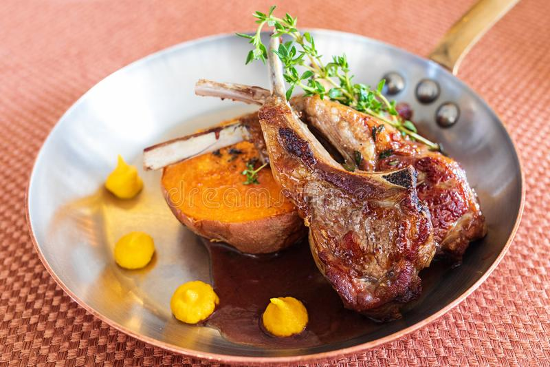 De geroosterde lamskoteletten van Nieuw Zeeland met geroosterde bataten, natuurlijke die saus met kruiden op smaak wordt gebracht royalty-vrije stock fotografie