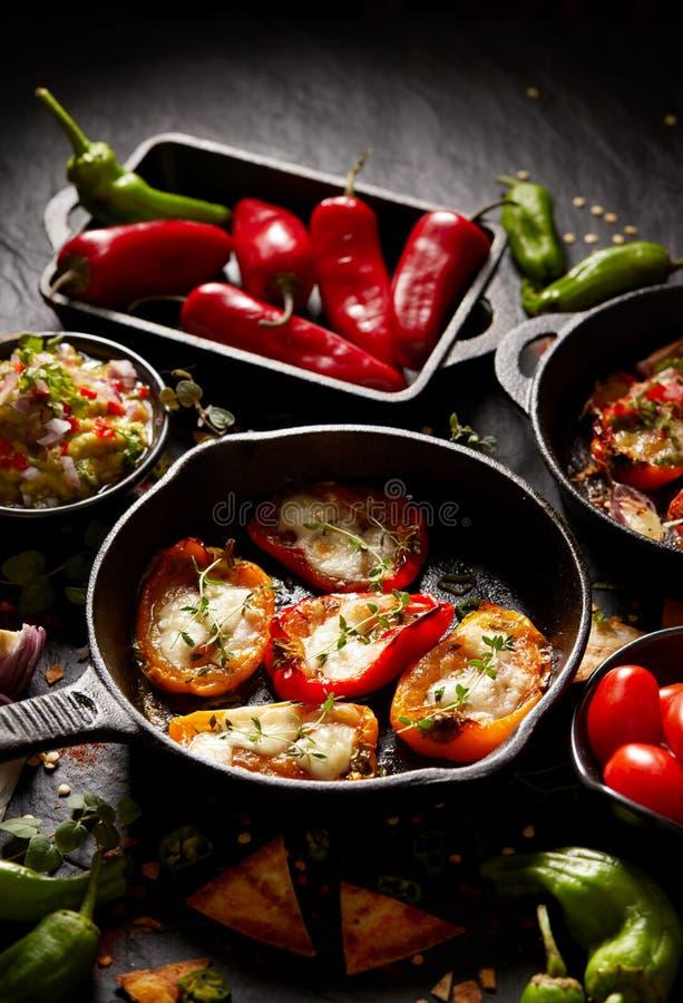De geroosterde paprika'spopcornpannen vulden met kaas en kruiden, mengeling van heerlijke voorgerechten stock foto