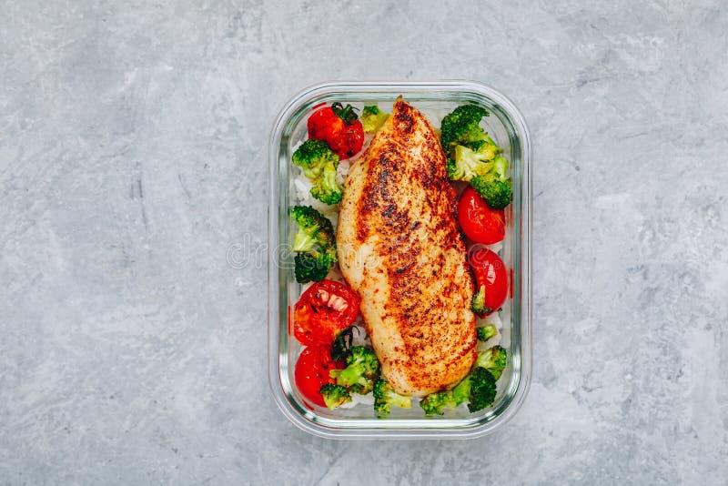 De geroosterde prep containers van de kippenmaaltijd met rijst, broccoli en tomaten stock foto's