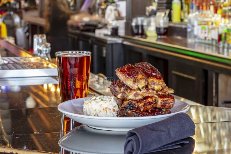 De geroosterde Ribben van de Varkensvleesbaby met Barbecuesaus op een Witte Plaat op een Houten Lijst stock afbeelding