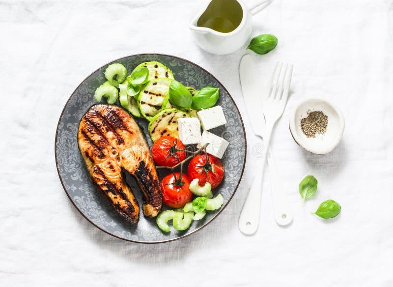 De geroosterde zalm, courgette, bakte kersentomaten en feta-kaas - gezonde evenwichtige maaltijd op lichte achtergrond stock fotografie