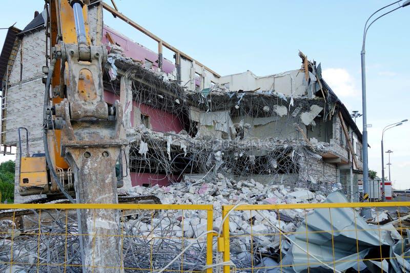 De geruïneerde bouw met meerdere verdiepingen Een graafwerktuig vernietigt een gebouw met meerdere verdiepingen met een beitelhul royalty-vrije stock afbeeldingen
