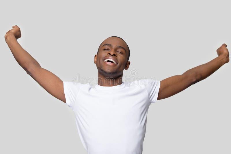 De geruste Afrikaanse opgeheven kerelhanden voelt opgetogen studioschot stock foto's