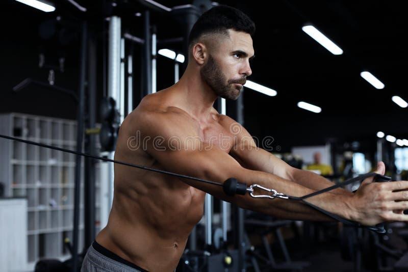 De geschikte en spiermens leidt pectoral spieren op een bloksimulator in op de gymnastiek royalty-vrije stock foto