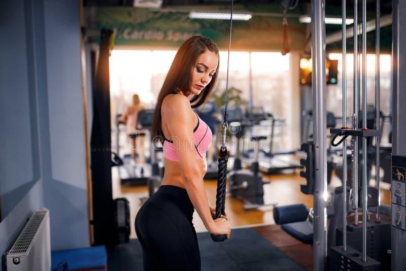 De geschikte triceps die van de vrouwentraining gewichten in gymnastiek opheffen stock fotografie
