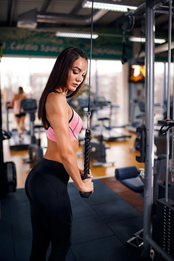 De geschikte triceps die van de vrouwentraining gewichten in gymnastiek opheffen royalty-vrije stock foto's