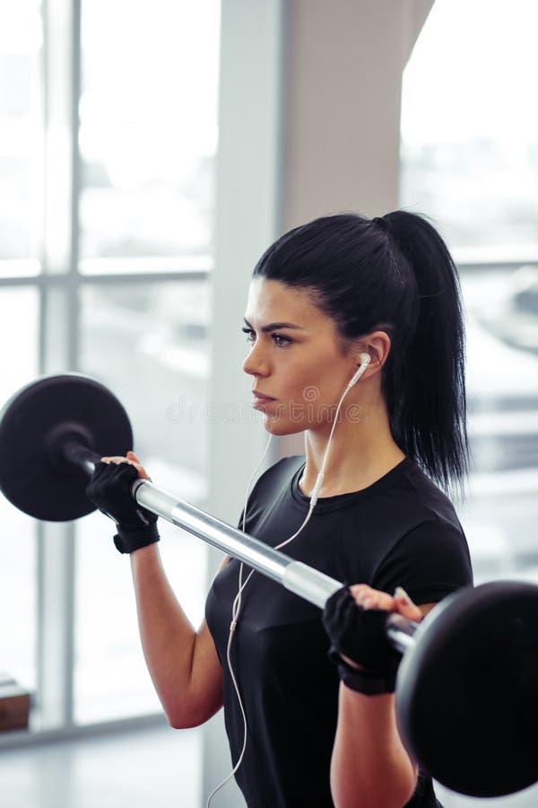 De geschiktheid, sluit omhoog van jonge vrouw verbetert voor bicepsen in gymnastiek royalty-vrije stock afbeeldingen