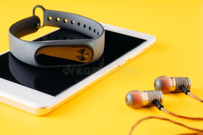 De de geschiktheidsdrijver, smartphone en hoofdtelefoons op gele achtergrond, sluiten omhoog stock foto