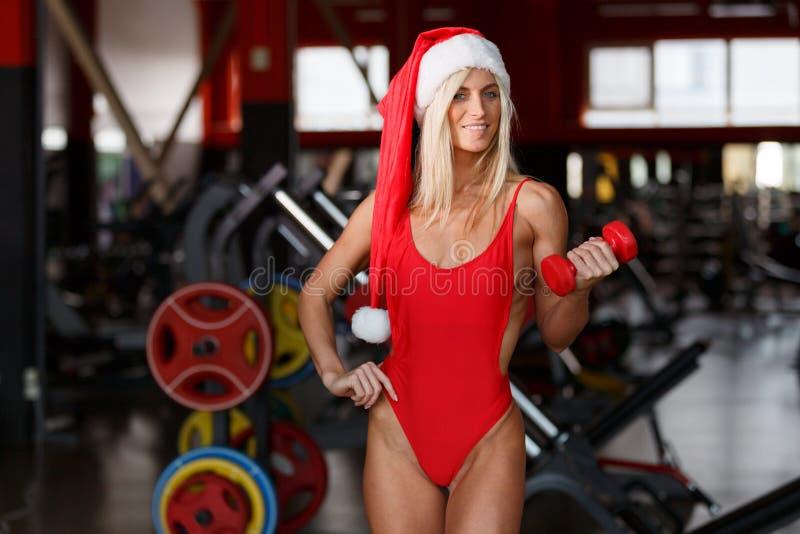 De geschiktheidsvrouw die een rood badpak dragen, die een Kerstmanhoed dragen, bevindt zich in gymnastiek het stellen royalty-vrije stock fotografie