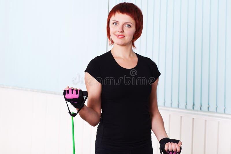 De geschiktheidsvrouw die van de roodharige oefening met expander doet royalty-vrije stock afbeelding