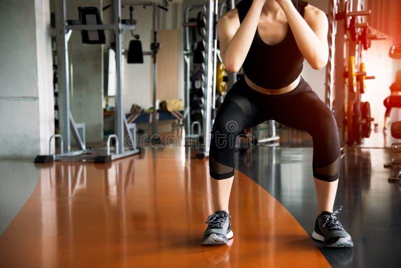 De geschiktheidsvrouw hurkende training voor het vette branden doen en de benen die stren stock afbeelding