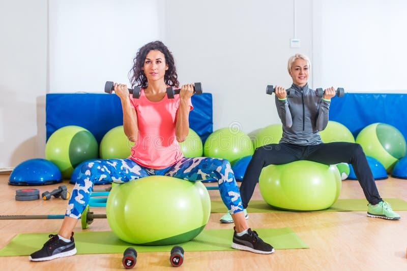 De geschiktheidsvrouwen die zitting op groene Zwitserse ballen uitoefenen die gezette bicepsen doen krullen het opheffen gewichte royalty-vrije stock afbeeldingen