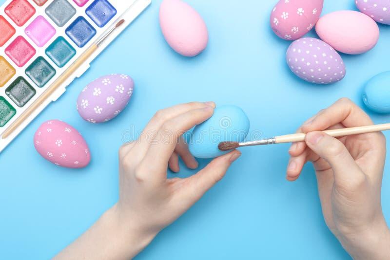 De geschilderde eieren van vakantiepasen hand met kip op de lijst stock foto