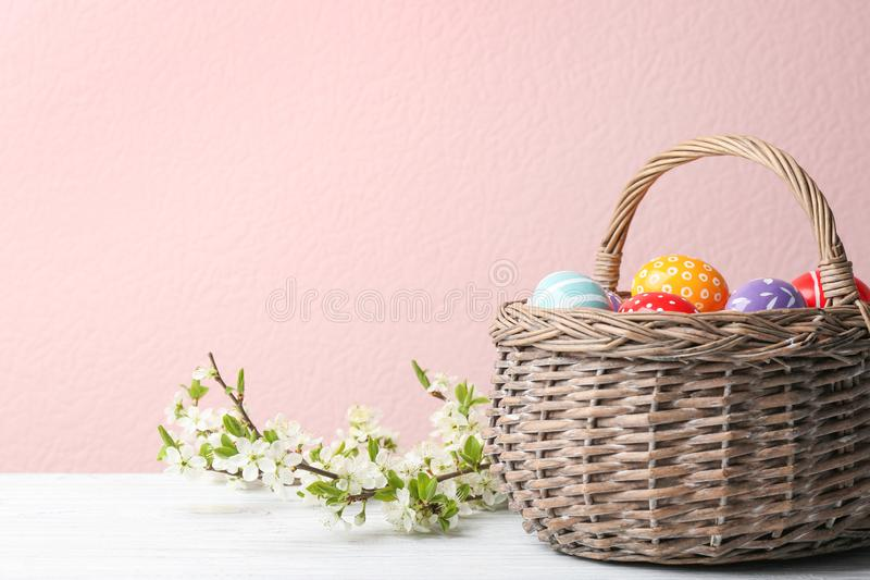 De geschilderde paaseieren in rieten mand en het tot bloei komen vertakt zich op lijst tegen kleurenachtergrond stock foto