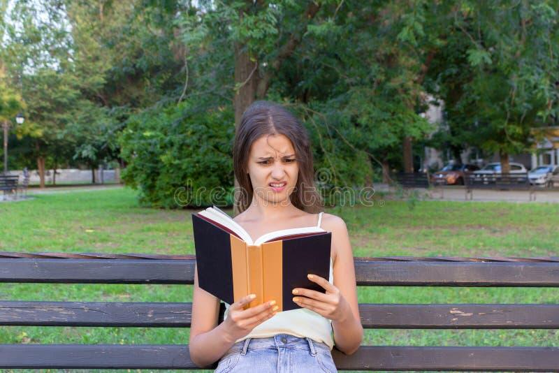 De geschokte en verraste vrouw houdt een boek en kijkt niet bevallen royalty-vrije stock afbeelding