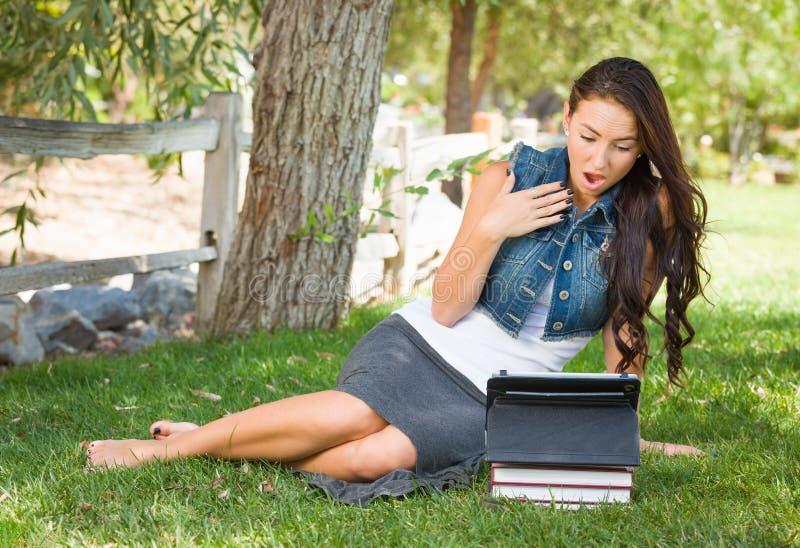 De geschokte Gemengde Ras Jonge Vrouwelijke Student With Books Using verwerkt gegevens royalty-vrije stock foto's
