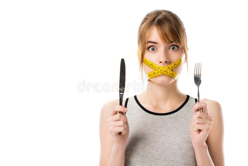 de geschokte jonge vrouw met het meten van band bond rond haar vork en mes van de mondholding royalty-vrije stock foto's