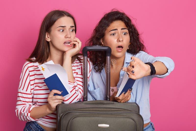 De geschokte jonge vrouwen die modieuze uitrustingen dragen die, die laat, horloge met doen schrikken gelaatsuitdrukking bekijken royalty-vrije stock fotografie
