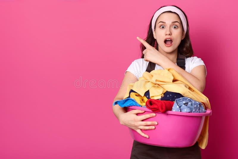 De geschokte Kaukasische huisvrouw met witte hoofdband, houdt bassin kleren, richt opzij met voorvinger, heeft verminderd adem, d royalty-vrije stock foto