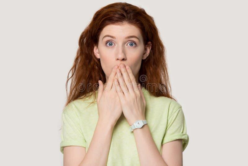 De geschokte mond van de roodharige vrouwelijke dekking met handen die camera bekijken royalty-vrije stock foto's