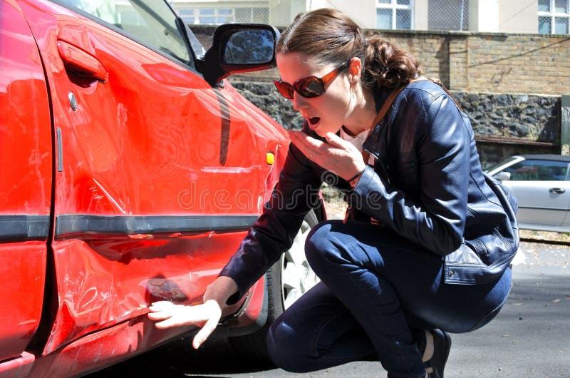 De geschokte vrouw kijkt een schade van haar auto stock fotografie