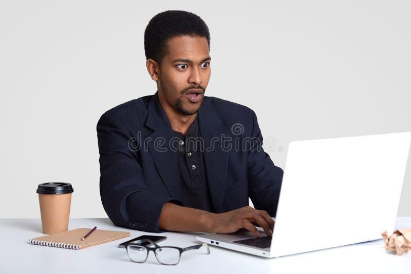 De geschokte zakenman met zwarte die huid, toetsenbordeninformatie over laptop computer, wordt bedwelmd om te ontbreken maakt pre royalty-vrije stock foto's