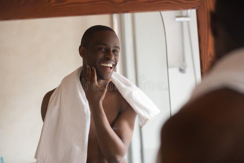 De geschoren knappe Afrikaanse mens die in spiegel kijken voelt tevreden stock afbeelding