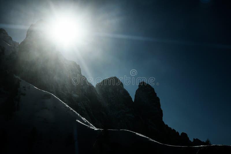 De de gesilhouetteerde hellingen en pieken van sneeuwbergen met zonstralen en gloed stock afbeelding