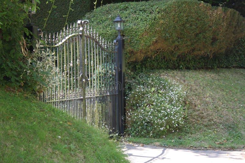 De gesloten die poorten van de ijzeroprijlaan door shrubbery worden omringd stock foto