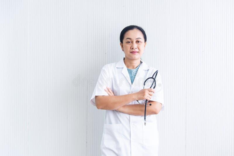 De gesloten omhoog zekere en glimlachende vrouw arts met witte eenvormig en het stethoscoopmedische apparaat op witte blackground stock foto's