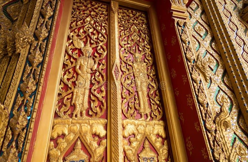 De gesloten rode poort van de Boeddhismetempel met gouden beeldhouwwerkverwezenlijking o royalty-vrije stock fotografie