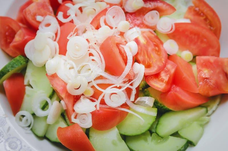 De gesneden tomaten, de komkommers en de uien zijn in ringen op een plaat Close-up, hoogste mening stock afbeelding