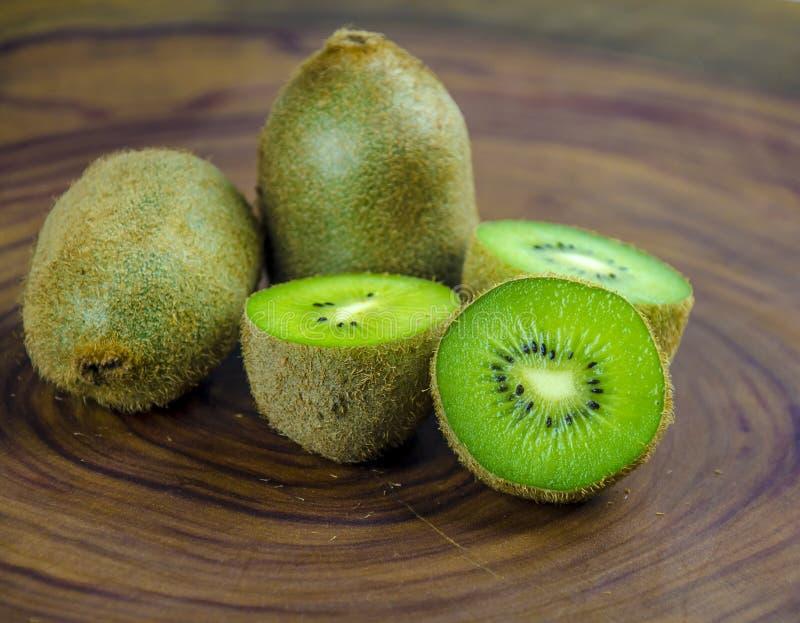 De gesneden verse en sappige helften van het kiwifruit op een houten achtergrond royalty-vrije stock afbeelding