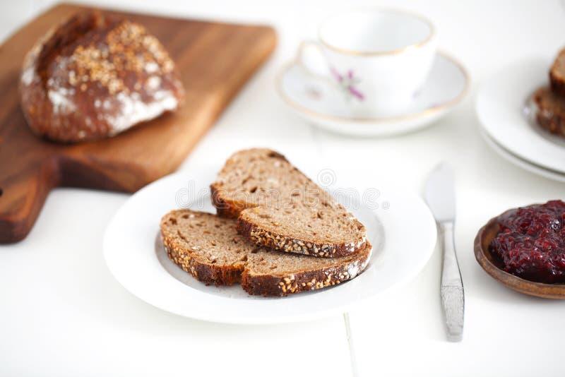 De gespelde gehele plakken van het korrelbrood met jam voor ontbijt stock foto's