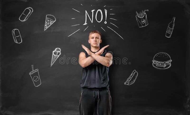 De gespierde jonge mens die eindeteken met zijn handen tonen en zegt nr aan ongezond voedsel op de achtergrond van bord stock afbeeldingen