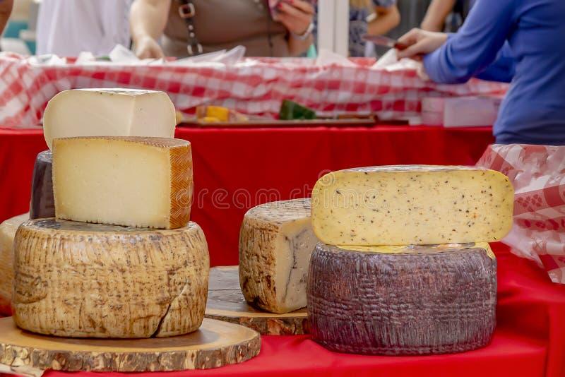 De gestapelde rondes van kaas worden getoond bij de openluchtlandbouwersmarkt terwijl de mensen winkelen royalty-vrije stock afbeelding