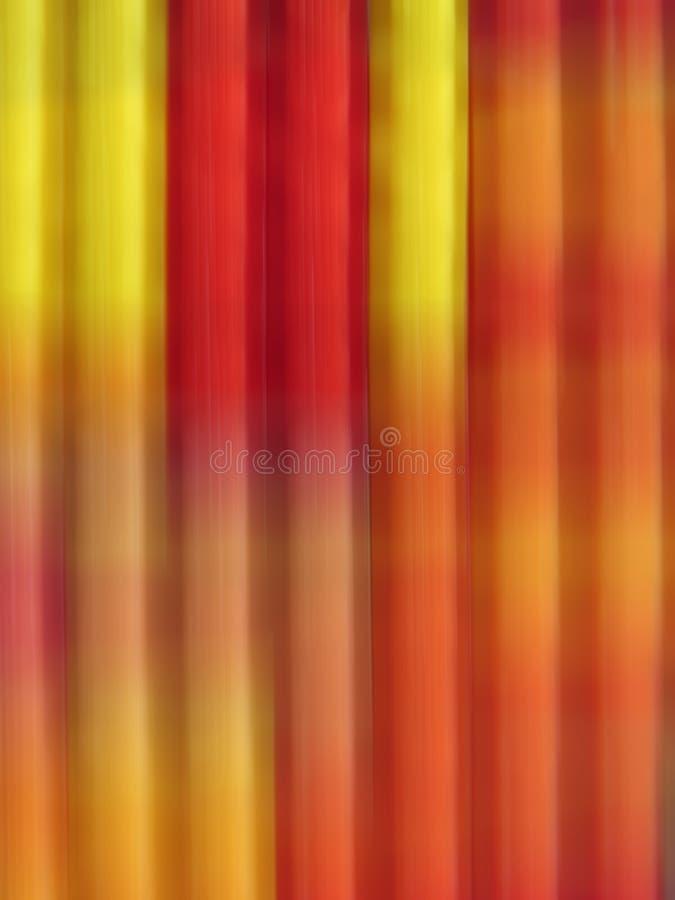 De gestreepte achtergrond in verticale motie blured lijnen in rood en geel royalty-vrije stock foto