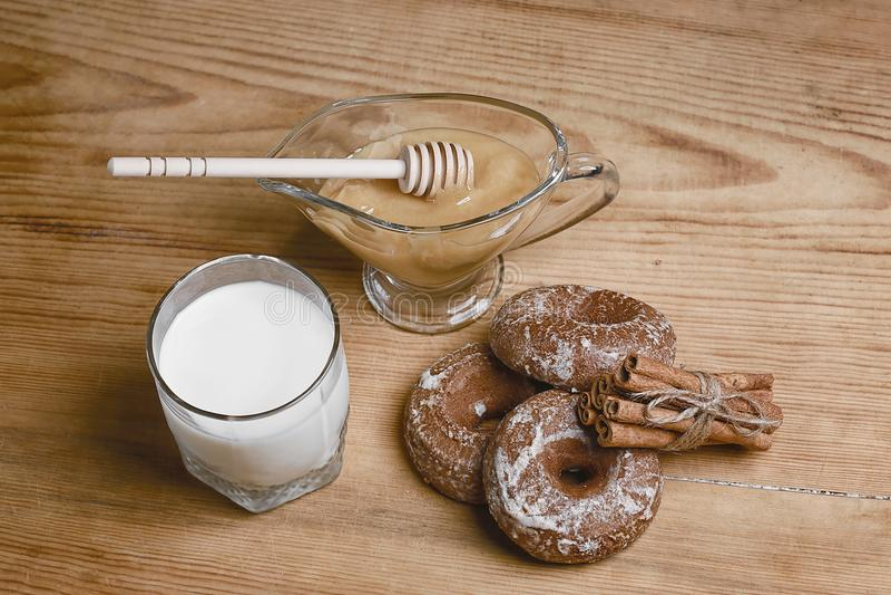 De geurige honingspeperkoeken, de cakes en een glas melk, honing, pijpjes kaneel bonden, houten lepel op een houten achtergrond,  stock fotografie