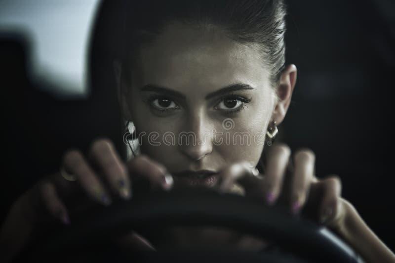 De gevaarlijke schoonheidsvrouw die een auto drijven, sluit omhoog portret stock afbeeldingen