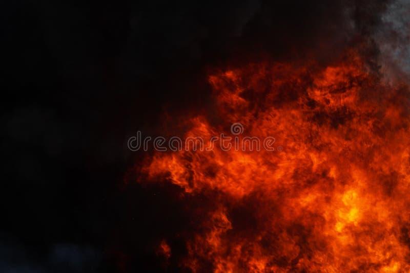 De gevaarlijke sterke rode vlammen van industriële brand en de dramatische zwarte rookwolken behandelden hemel stock foto