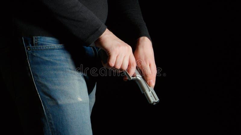 De gevaarsmens herlaadt een pistool stock foto